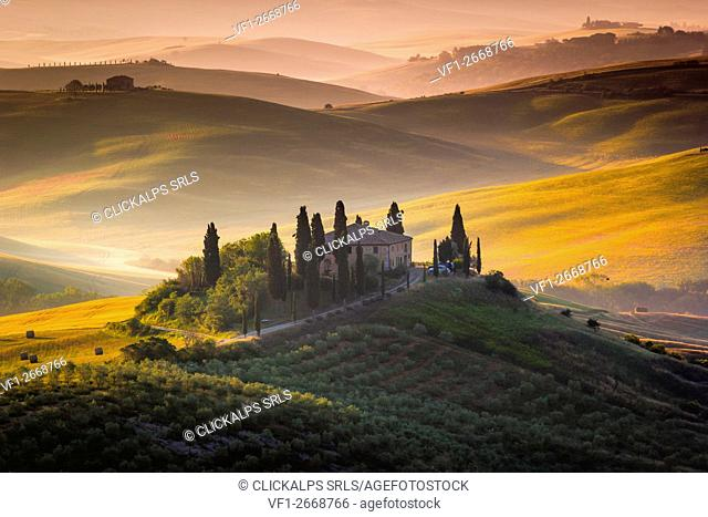 Tuscany, Val d'Orcia, Italy. Sunrise over the green and golden hills, with lonely farmhouse and cypress trees