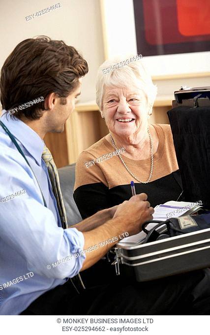 Doctor visiting senior woman at home