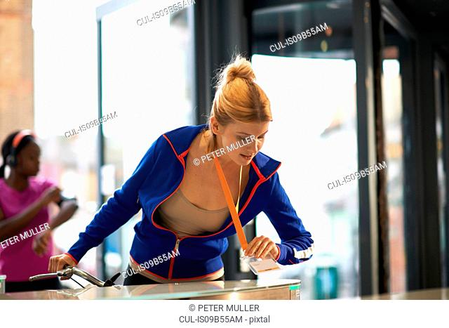 Woman tapping on security barrier on arrival at work