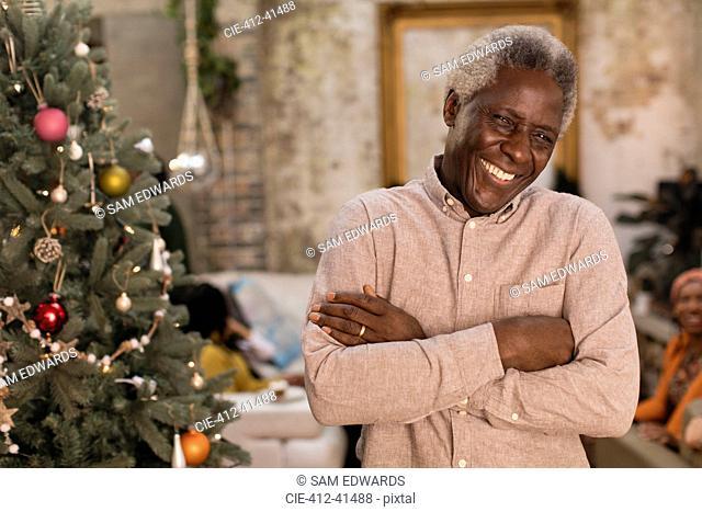 Portrait smiling, confident senior man next to Christmas tree