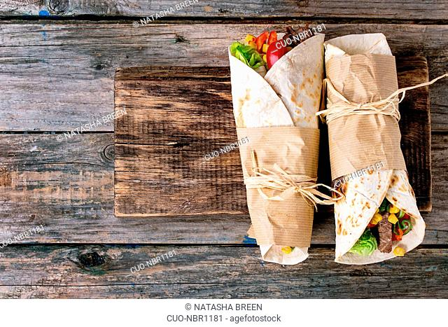 Mexican style dinner. Two papered tortillas burrito with beef and vegetables over old wooden background. Flat lay. With copy space