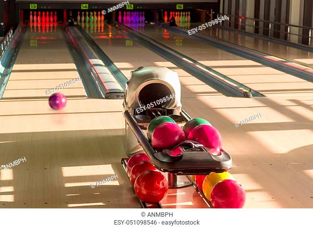 Playing area with several lanes with bowling pins, bowling ball rolling along the lane and colored bowling balls on the foreground in the modern pin bowling...