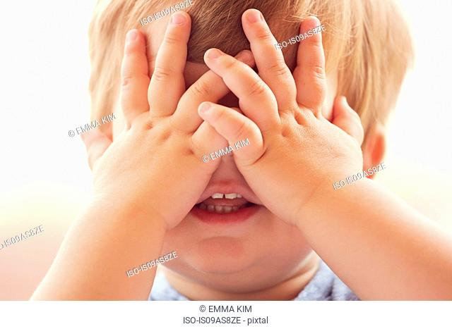 Cropped portrait of young boy covering his eyes with his hands