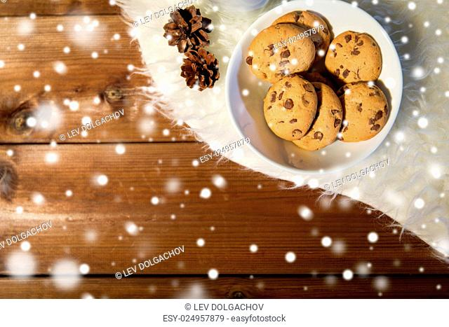 holidays, christmas, winter, advertisement and food concept - close up of cookies in bowl and cones on white fur rug on wooden board