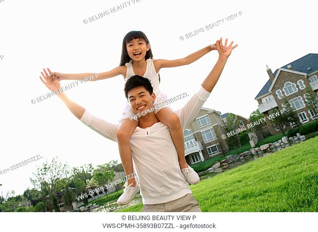 A girl sitting on father's shoulders on the grass