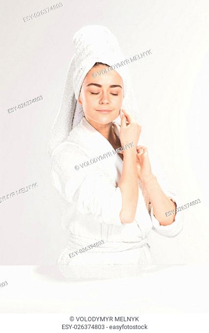 Woman cleaning face in bathroom on gray background