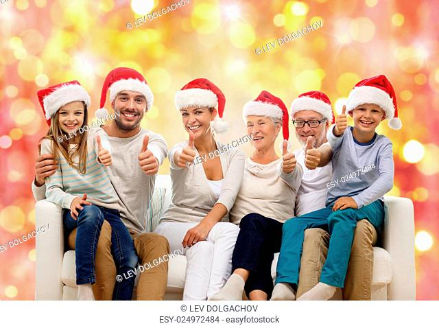 family, happiness, generation, holidays and people concept - happy family in santa helper hats sitting on couch and showing thumbs up gesture over lights...