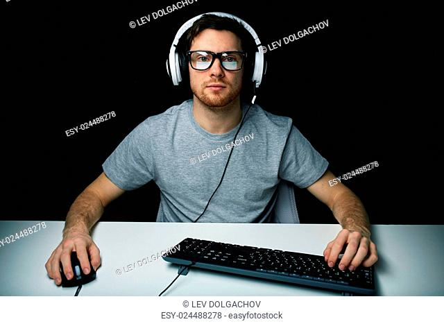 technology, gaming, let's play and people concept - young man or hacker in headset and eyeglasses with pc computer playing game and streaming playthrough or...