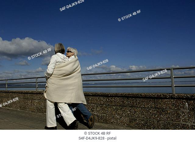 Two mature women wrapped in a blanket walking along the Baltic Sea