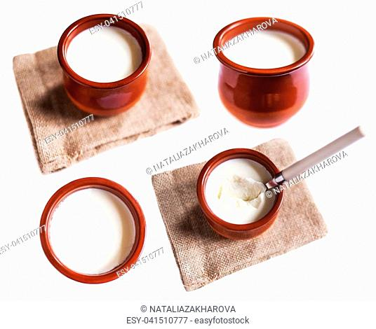 Yogurt cream or Cottage cheese curd in clay pot isolated on a white background. Traditional Cuajada sour cream