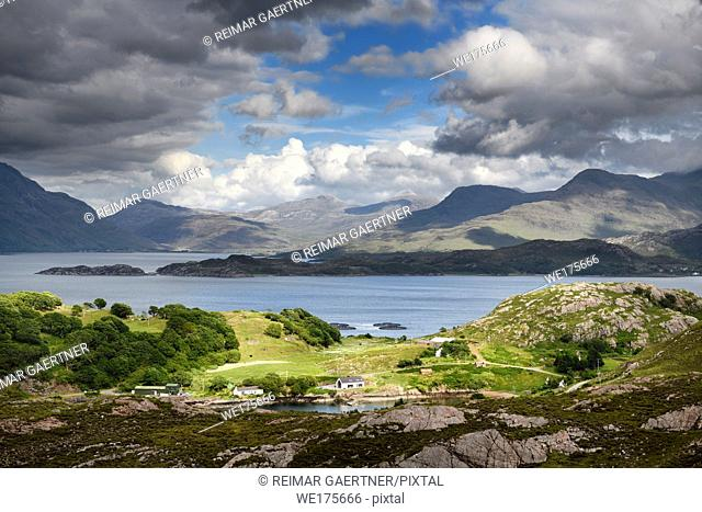 Sun on Ardheslaig village on Loch Beag and fish farm on Loch Shieldaig and Torridon Hills at Upper Loch Torridon Scottish Highlands Scotland