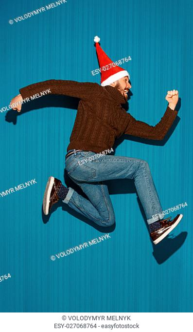 The running christmas man wearing a santa hat on the blue studio background