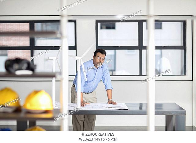 Man with blueprint and wind turbine models in office