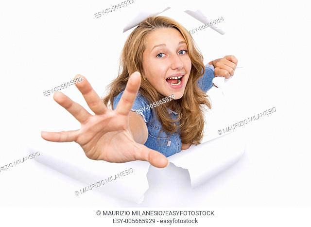 Young woman coming out of a hole tearing on the white paper