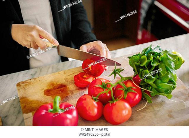 A woman using a sharp knife, slicing tomatoes