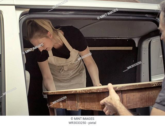 Two people, a man and a young woman lifting an antique wooden table into the back of a van