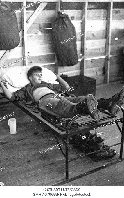 A United States Army serviceman laying on the springs of a bed without a mattress covering them, duffel bags are hanging from the walls of the barracks while a...
