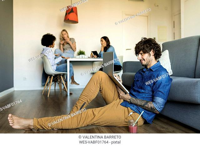 Smiling man sitting on floor using laptop with friends in background