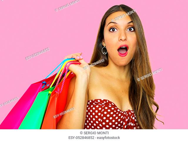 Portrait of a pretty shocked fashion girl holding shopping bags isolated over pink background