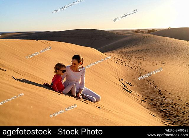 Mother and daughter sitting in sand dunes, Gran Canaria, Spain