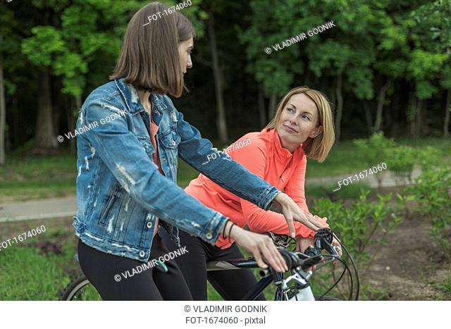 Mother and daughter talking while sitting on bicycle against trees at park