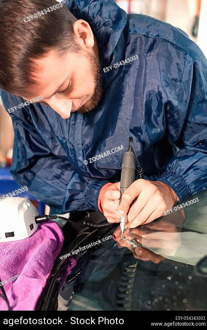 Close up Car glaze worker fixing and repairing a windshield or windshield of a car at a garage service station. Drill glass for repair