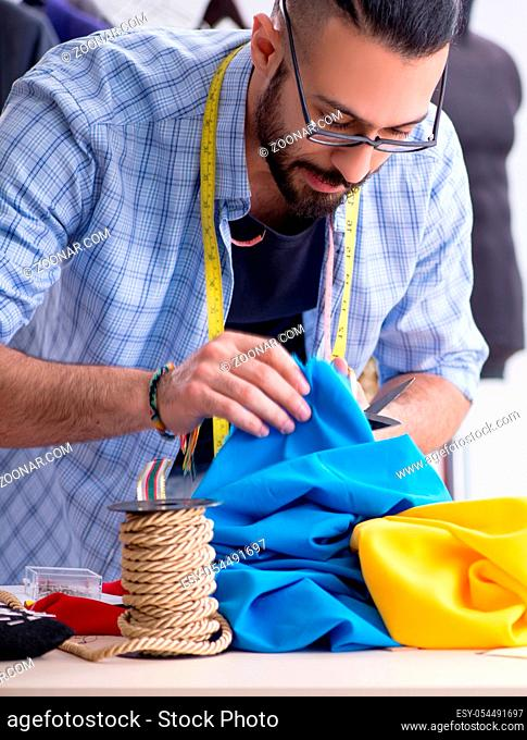 The male tailor working in the workshop on new designs