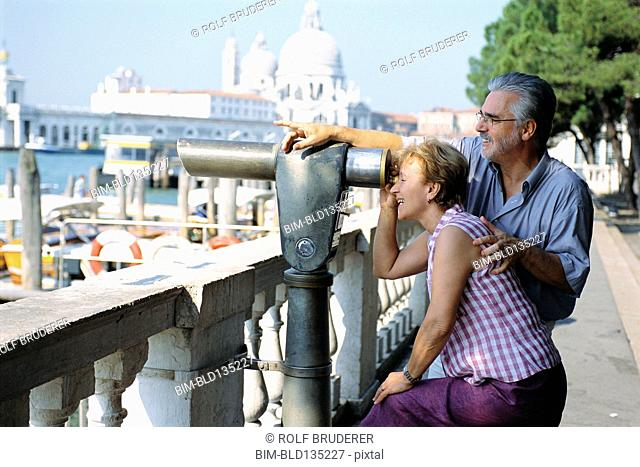 Senior couple looking through telescope, Venice, Veneto, Italy