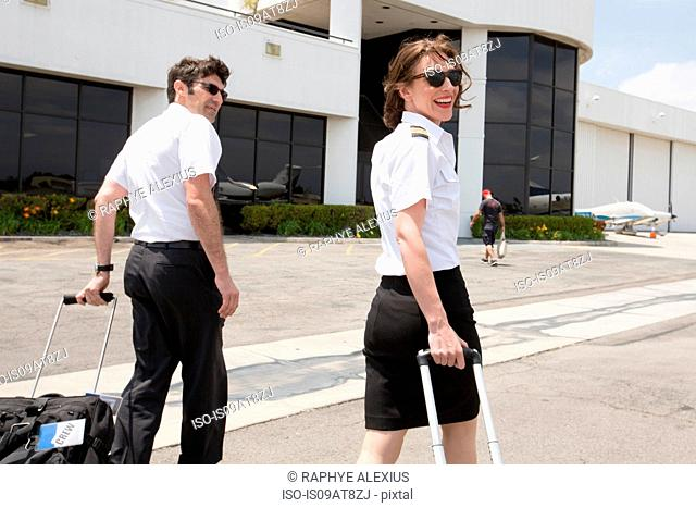 Male and female pilots pulling wheeled suitcases at airport