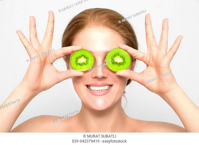 Woman with kiwi slices in front of her eyes