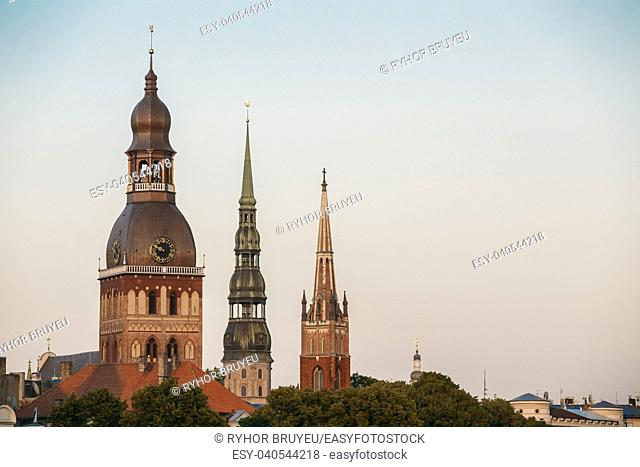 Riga, Latvia. Close View Of Three Towers With Steeples Of Riga Cathedral, St. Peter's Church And St. Saviour's Anglican Church In Old Town In Summer Under Blue...