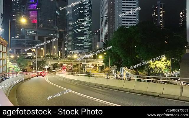 Hong Kong at night. Large traffic interchange between skyscrapers. Car traffic. Fast motion