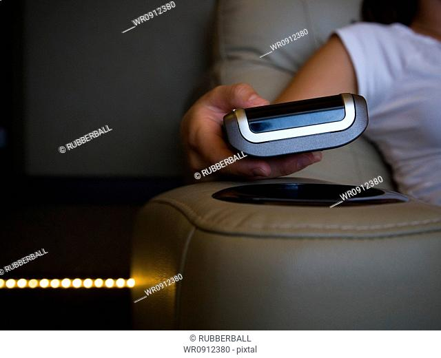 Hand holding remote control in home theater