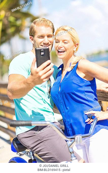 Caucasian couple taking selfie with cell phone
