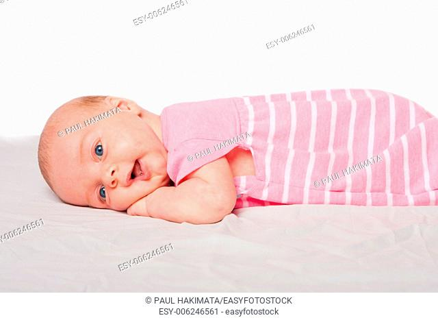 Cute happy baby infant girl laying on belly tummy, on white