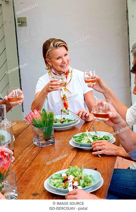 Woman toasting at lunch with friends in restaurant