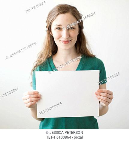 Portrait of young attractive woman holding blank sheet of paper