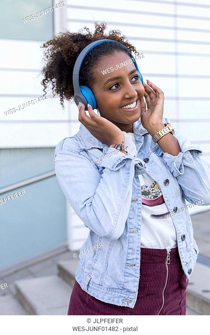 Portrait of smiling young woman listening music with headphones