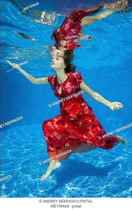 Young pregnant woman in red dress under water in the pool