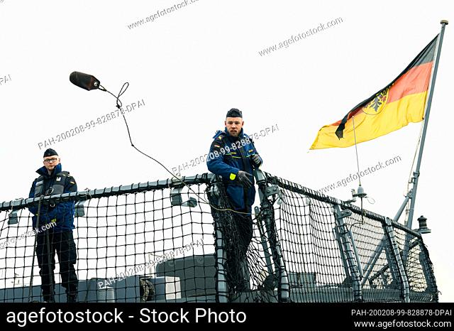"""08 February 2020, Lower Saxony, Wilhelmshaven: A marine soldier of the frigate """"""""Hamburg"""""""" throws a line to another soldier standing at the port after returning..."""