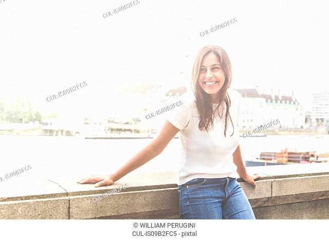 Young woman leaning on wall, London Eye in background, Embankment, London, England
