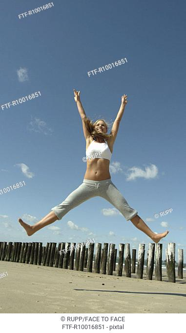 A woman in mid air is seen stretching her body near the pegs on the beach