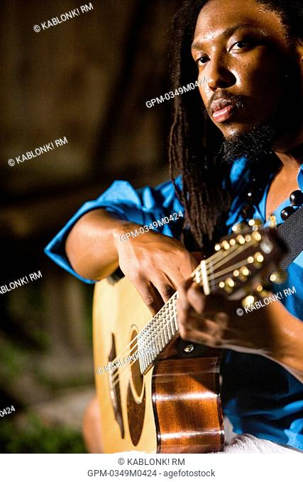 Young Jamaican man with dreadlocks holding guitar on tropical island