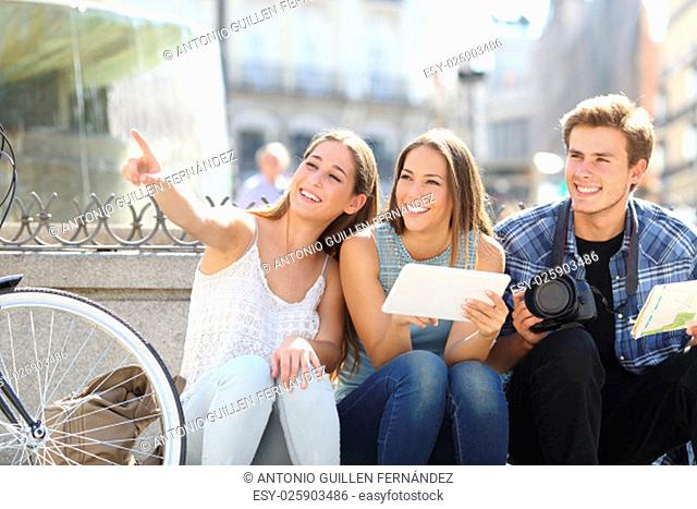 Tourist friends searching locations sightseeing in a city street