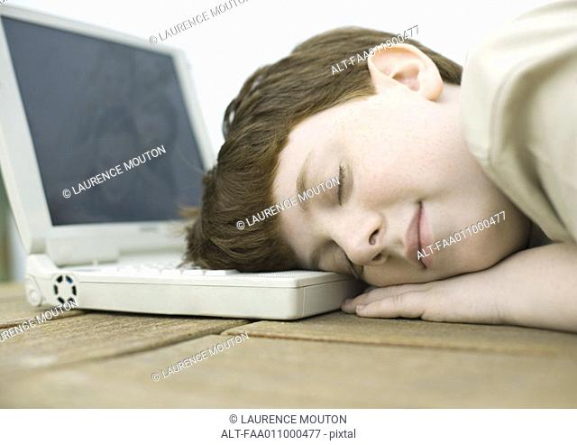 Boy sleeping with head on laptop