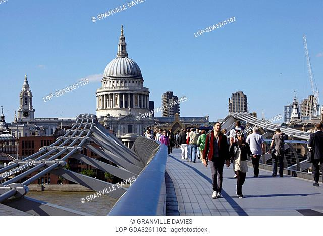 England, London, Millennium Bridge. People crossing the Millennium Bridge over the River Thames connecting St Pauls Cathedral on the north bank to Bankside on...