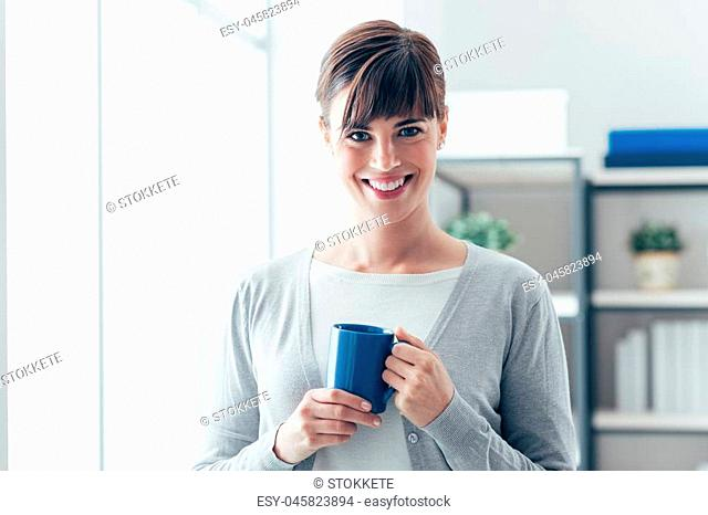 Attractive young woman holding a mug and having an hot coffee next to a window, she is smiling at camera
