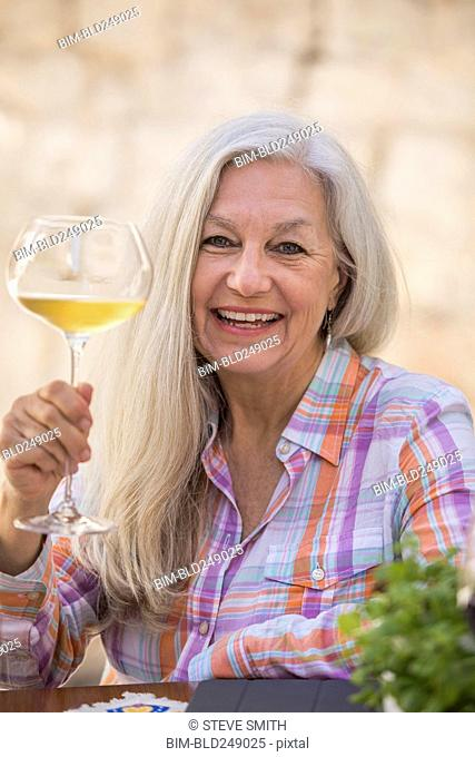 Smiling older Caucasian woman holding white wine