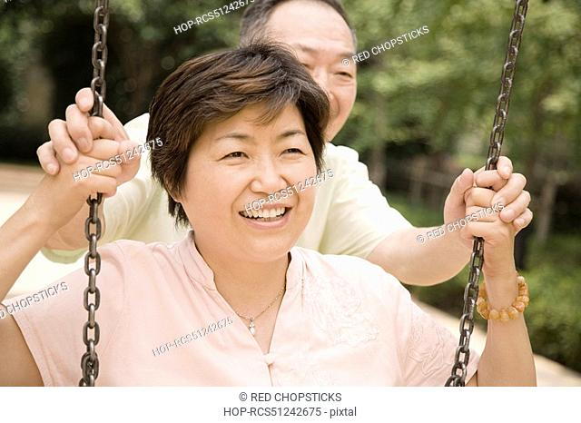 Senior man pushing a mature woman on a swing
