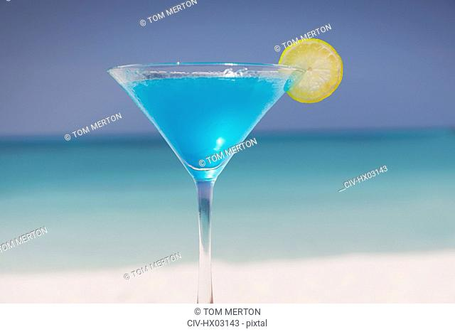Blue cocktail with lemon slice in martini glass on tropical ocean beach